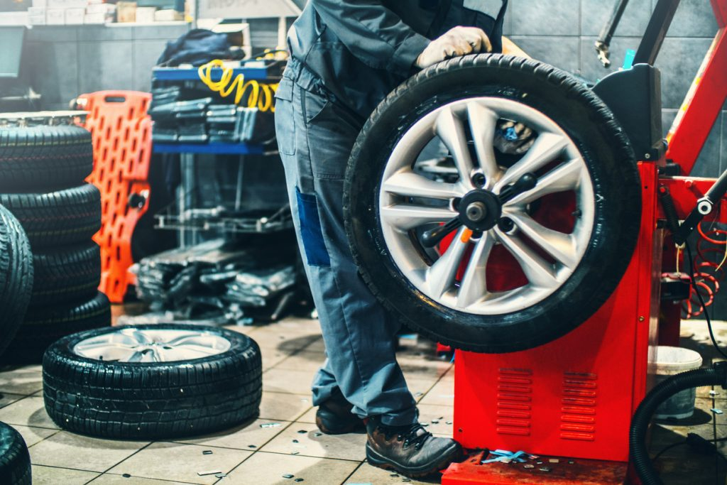 Auto mechanic performing work on tires