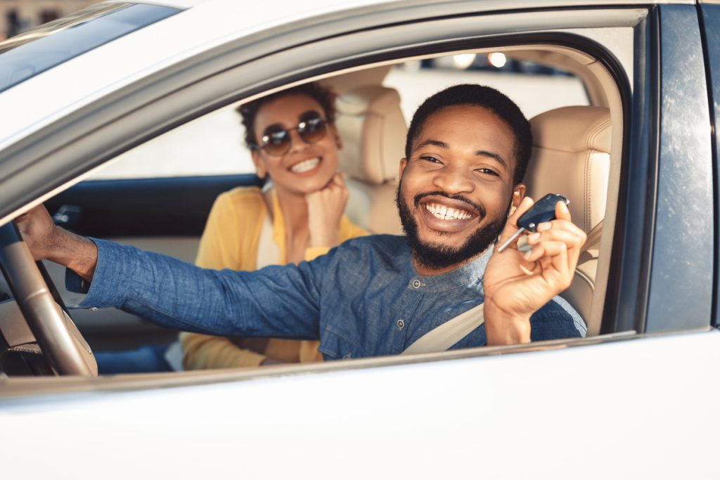 A couple in a white sedan showing off their new car and key.