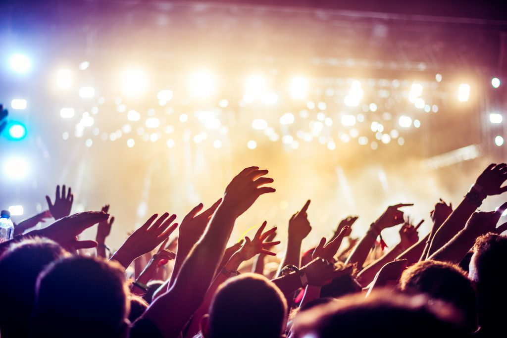 Audience with hands raised at Greenville Concerts
