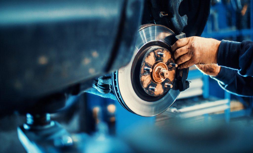Mechanic replacing car brake pads.