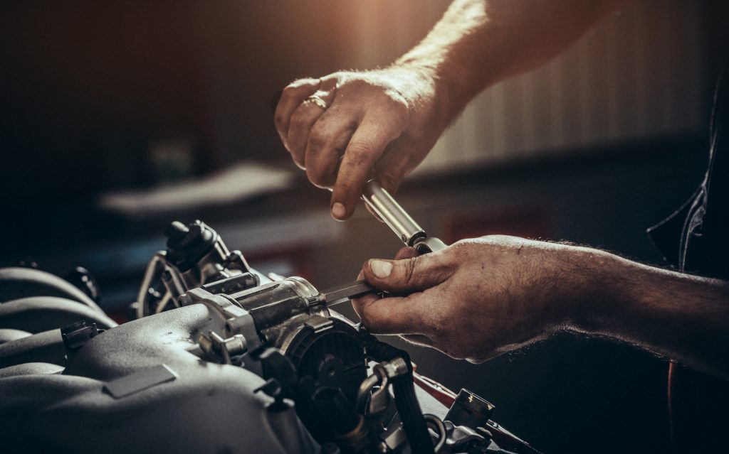 Mechanic's hands working under the hood of a car