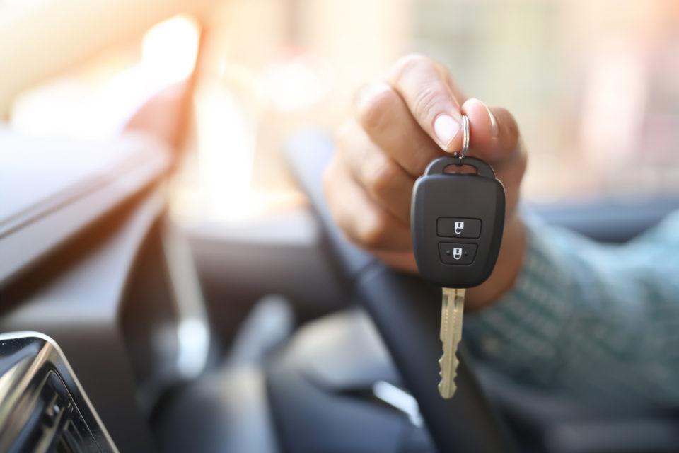 A man's hand holding a car key