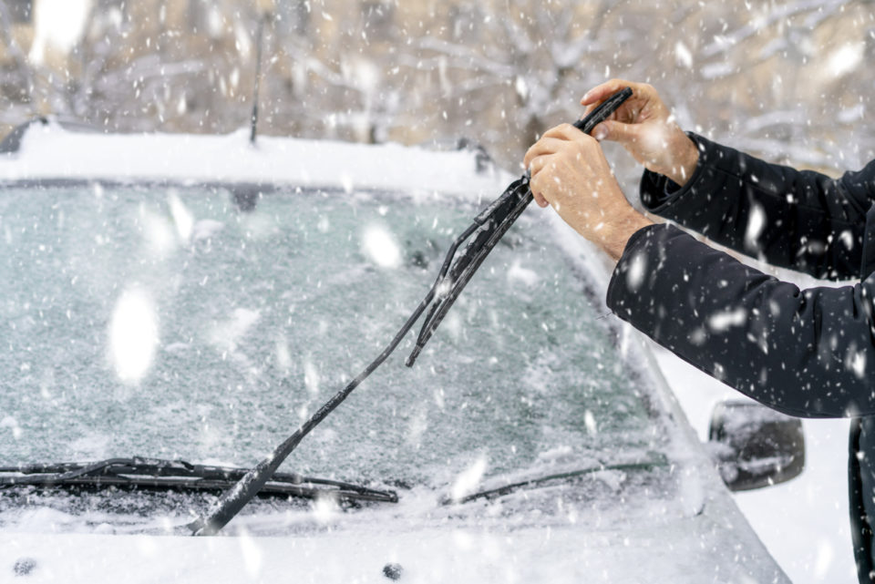 man adjusting and cleaning wipers of car in snowy weather