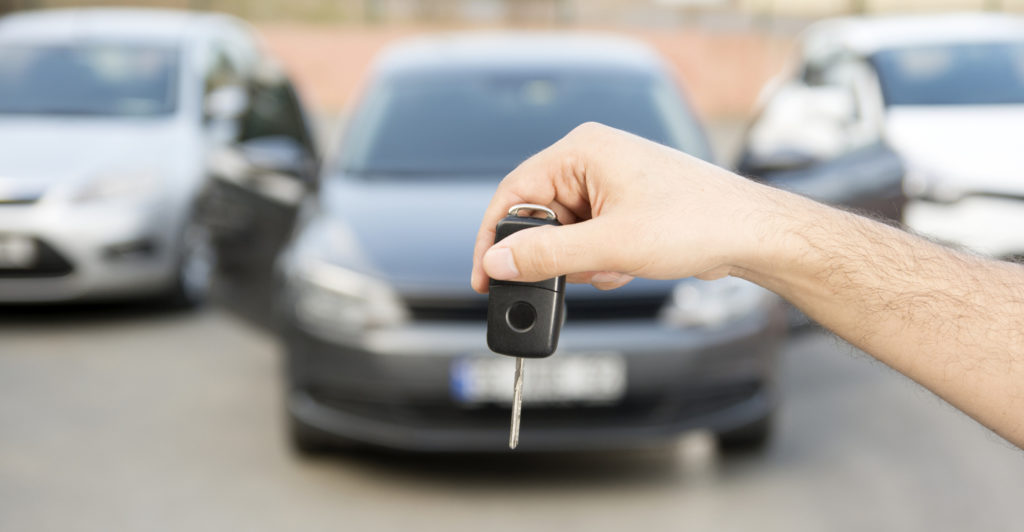 Human standing in front of the car they just bought with keys in hand.