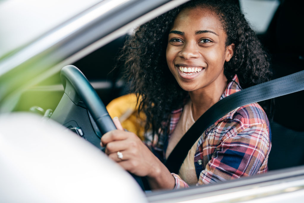 Smiling woman behind the wheel of a car
