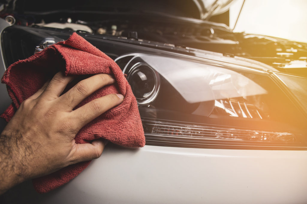 hand cleaning car's exterior with microfiber towel