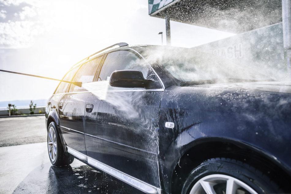 High-pressure washing car outdoors.