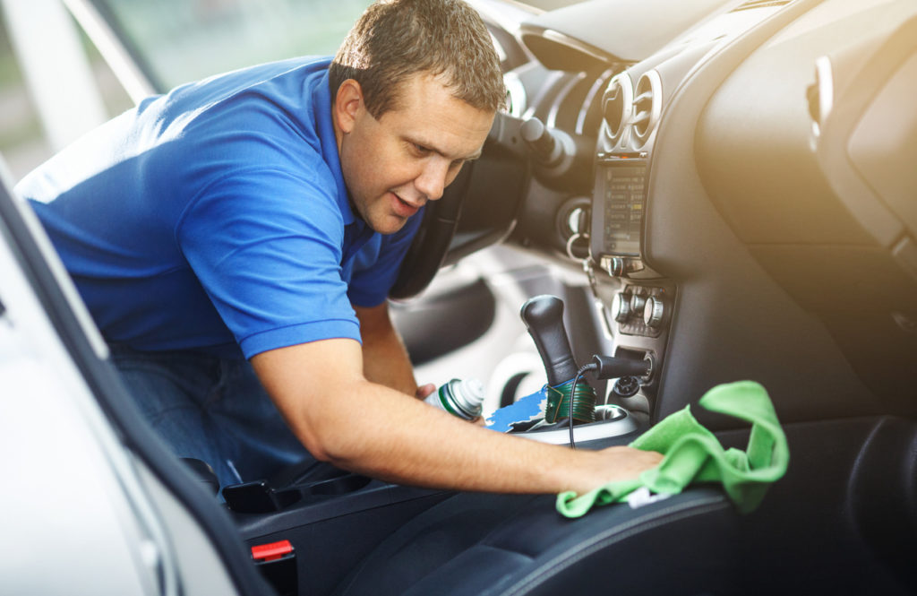 Mid-aged man cleaning the interior of his car