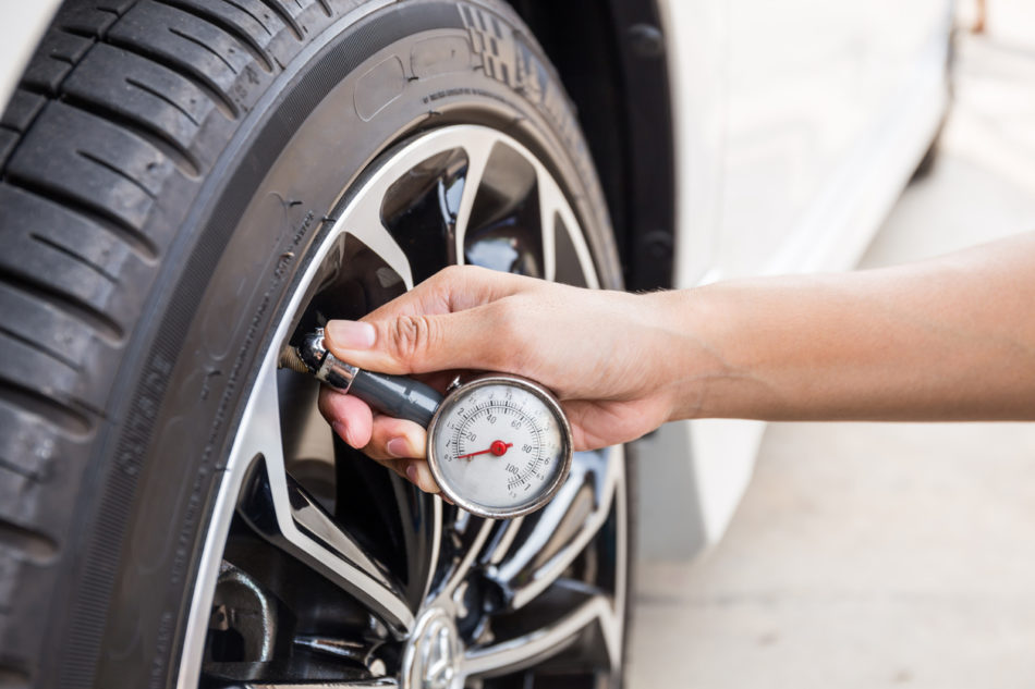 Close-Up Of Hand holding pressure gauge for car