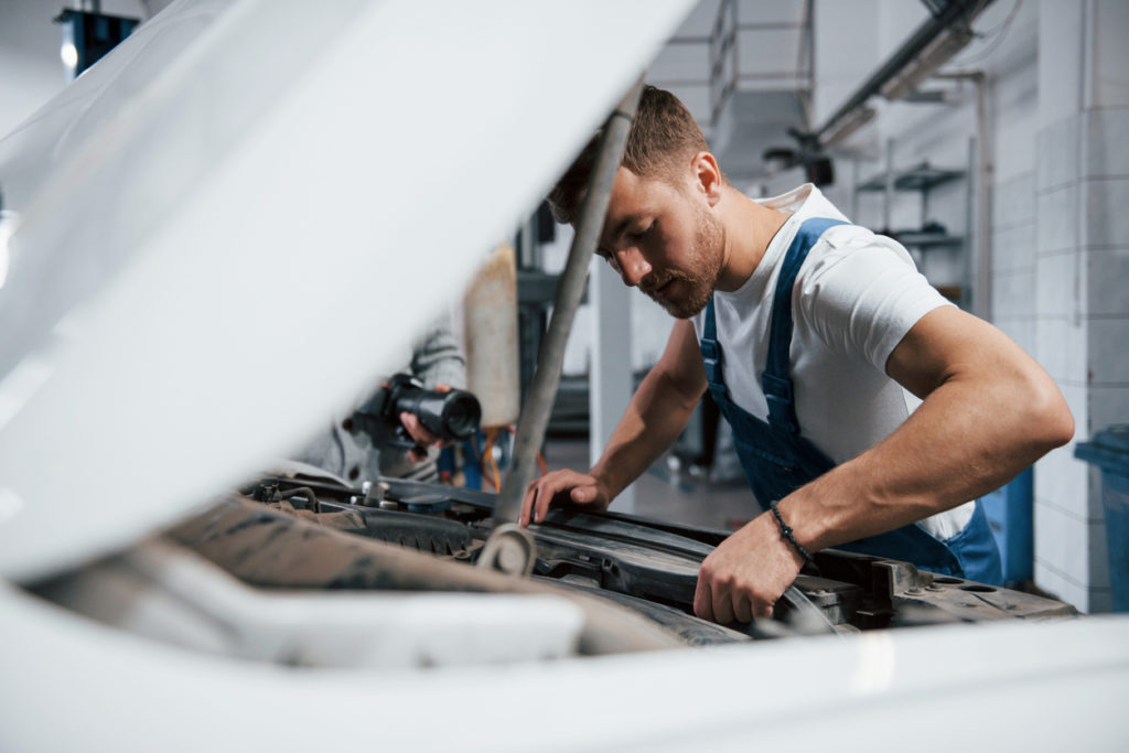 auto technician working under the hood of a vehicle