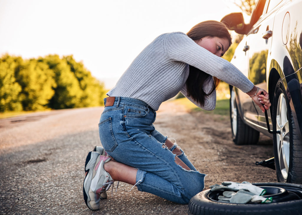 Woman changing wheel after a car breakdown at the side of the road.
