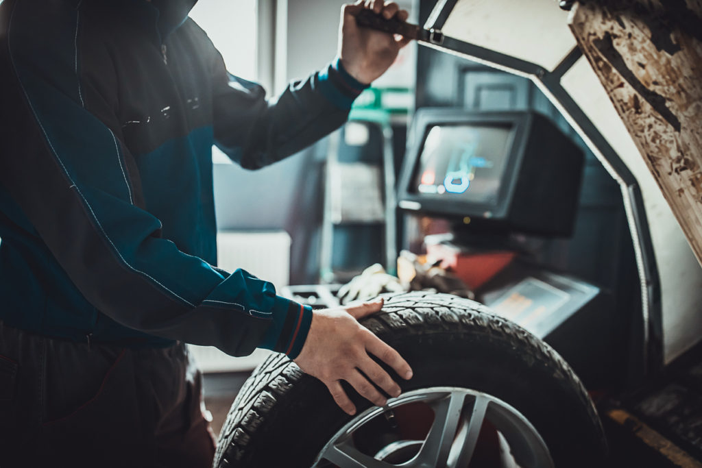 One young mechanic balancing a tire in auto repair shop.