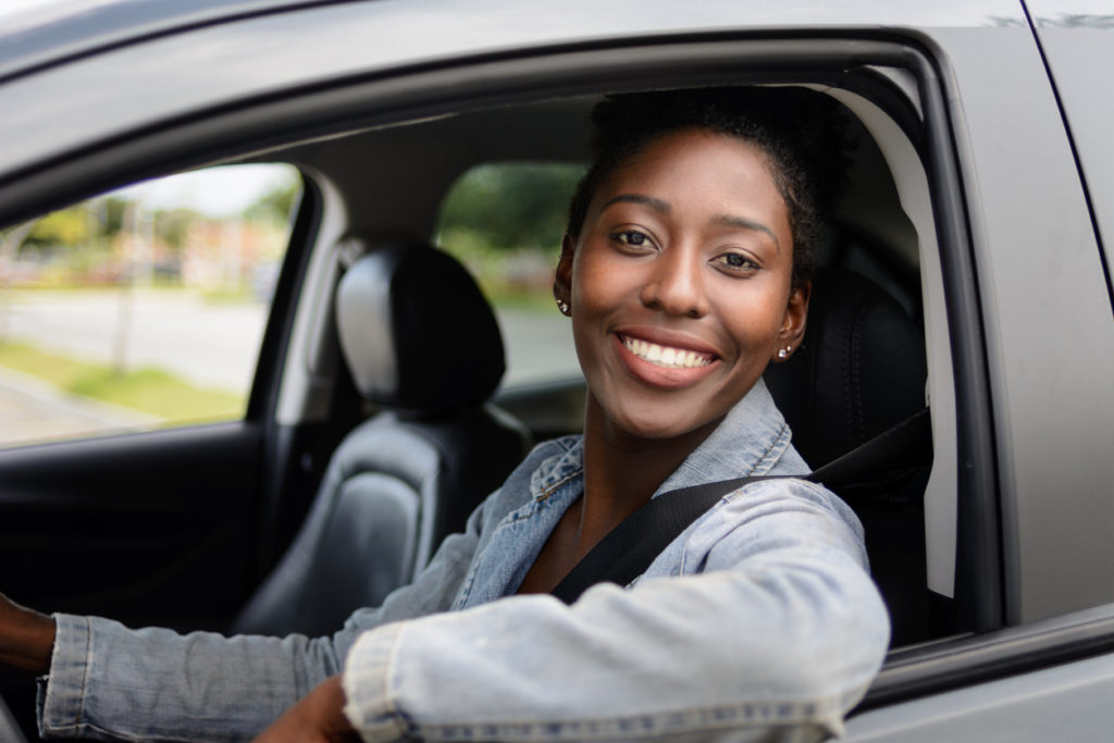 Portrait of young woman driving a car