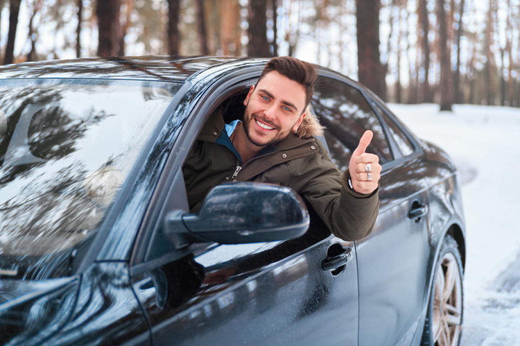 man sits at the wheel of his car sunny winter day shoeing thumbs up gesture. Wintertime road trip.
